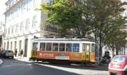 Eine alte Straßenbahn fährt durch Lissabon