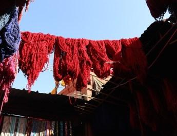Rot gefärbte Wolle hängt zum Trockenen über den Gängen des Souks in Marrakesch