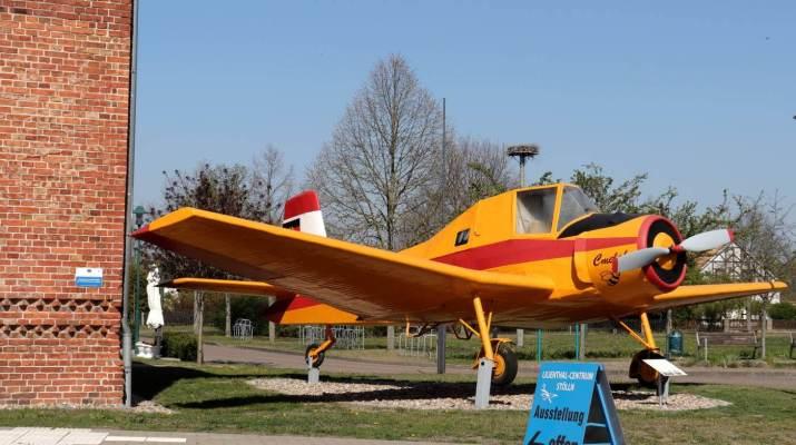 Ein Flugzeug in strahlendem Gelb steht vor dem Lilienthal-Centrum in Stölln