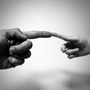 Gemeinsam Spaß haben: Vaterhand berührt Kinderhand
