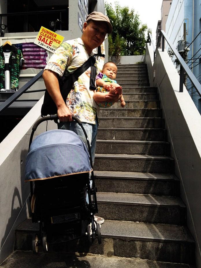 階段にて。赤ちゃんとベビーカーを担いであがる。