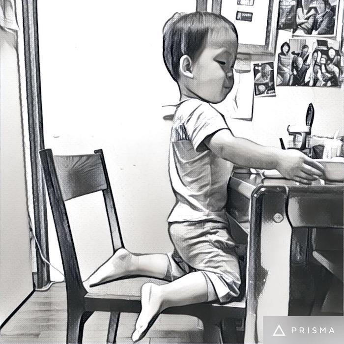 大人のダイニングチェアに座って食べる2歳の息子