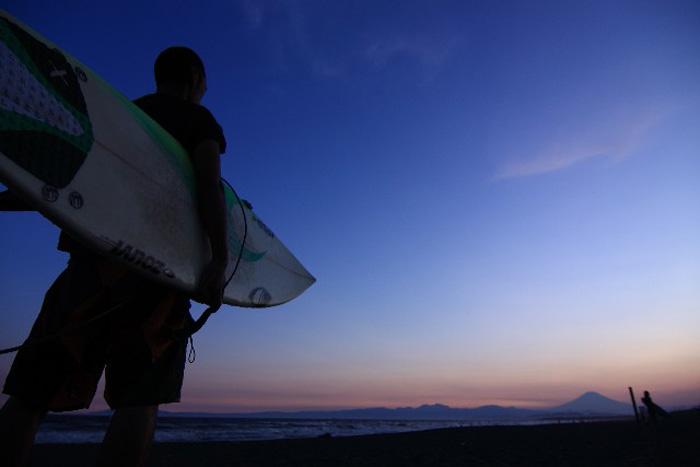 サーフボードを抱える男性