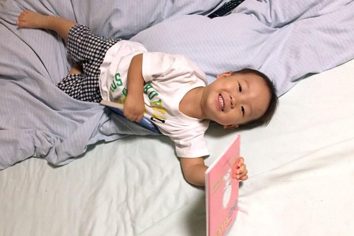 大好きな絵本を持ってベッドでごろごろする息子