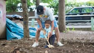 息子とショベルで土を掘る父親