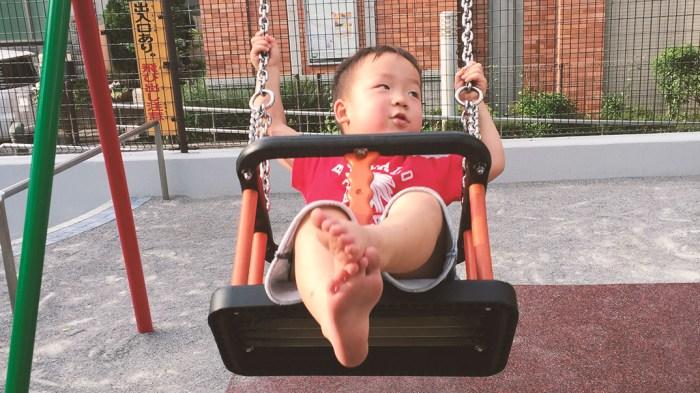 幼児用ブランコに乗る子供