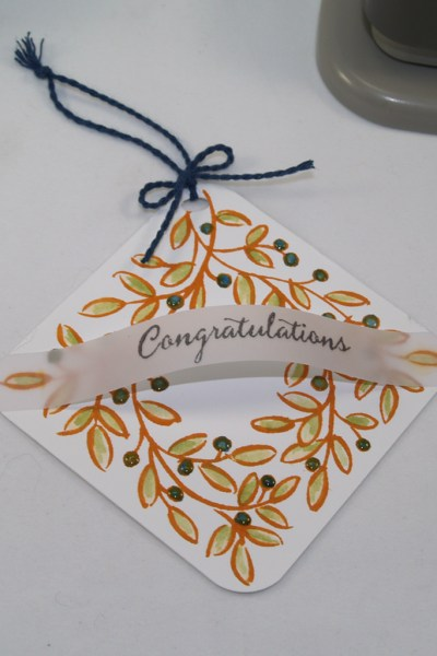 Square wreath tag with arched congratulations sentiment created using the Feathers & Frost and Balloon Celebration Stamp Sets from Stampin' Up!