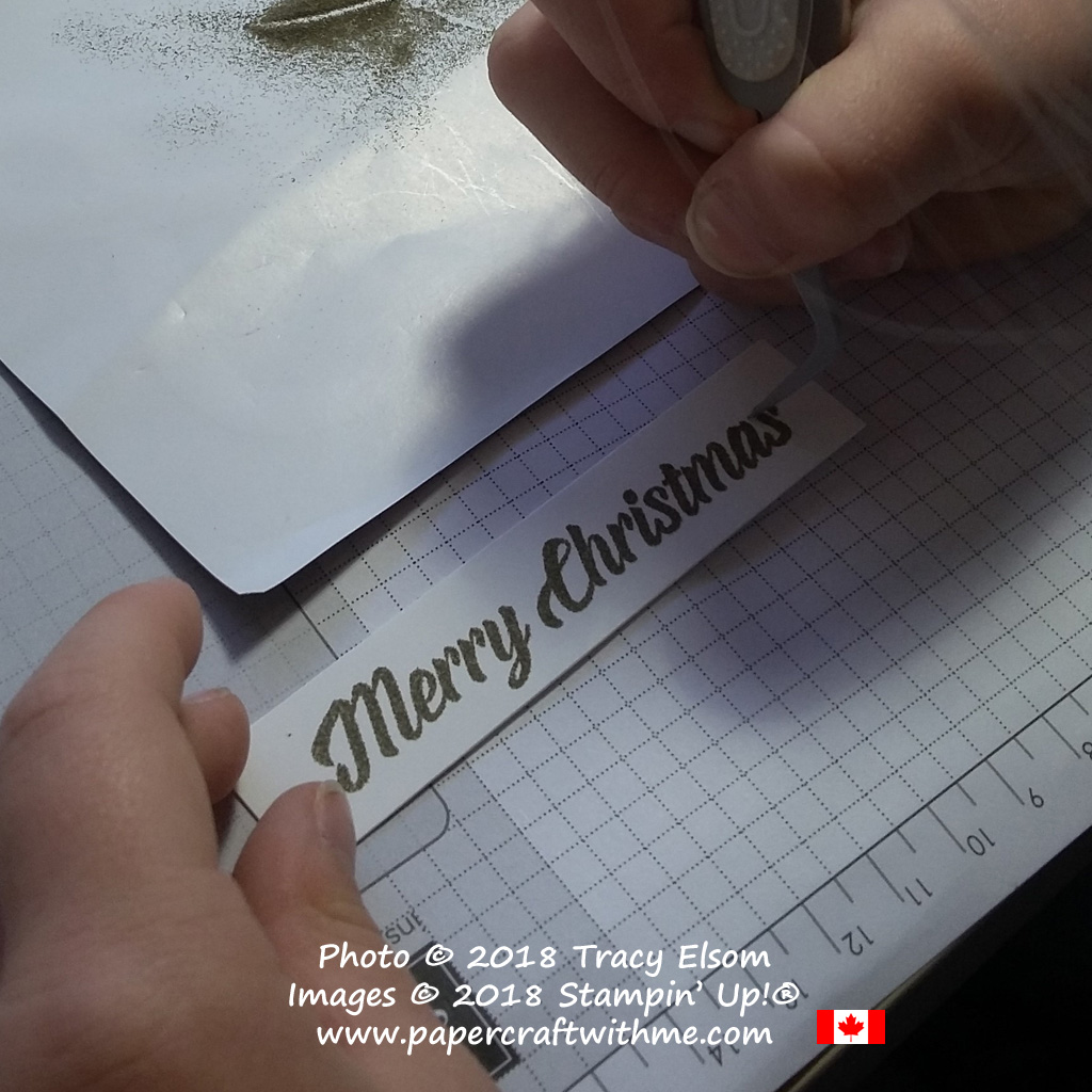"""Removing stray specks of powder before embossing the 'Merry Christmas"""" sentiment."""