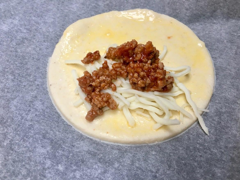 Pensle med pisket egg og melk rundt kanten, og brett delen uten fyll over delen med fyll.
