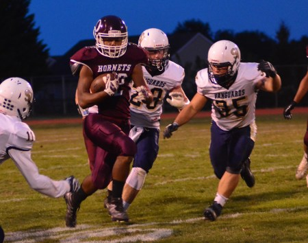 Oxford's Tim Davis hits the hole with Charlie Wendling and Rocky Albano in pursuit for Sun Valley.  Davis led all rushers with 137 yards on 20 carries before leaving the game with an inury