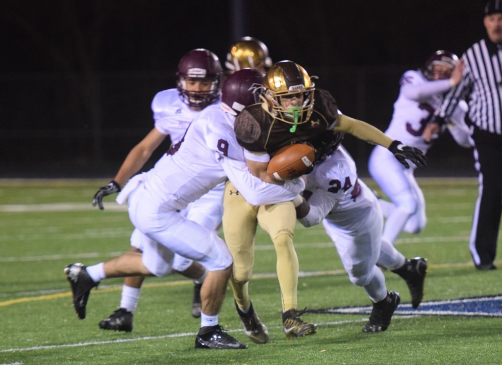 Pottsgrove's Ryan Finn (9) and Nehemiah Collins (24) team up to force a fumble from Bethlehem Catholic's Nicholas Petros in the second quarter Friday at Northern Lehigh High School. (Austin Hertzog - Digital First Media)