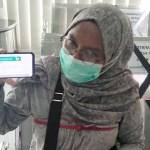 Siti sedang menunjukkan aplikasi Mobile JKN-KIS. PbP/EKA