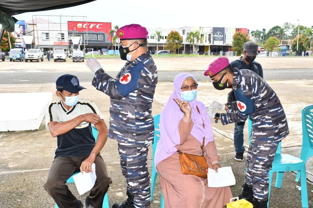 Caption: Warga yang tampak bersemengat mengikuti kegiatan serbuan vaksinasi yang dilakukan Pasmar 3 TNI AL di Alun-Alun Aimas, Senin (19/7/2021). Foto: Istimewa