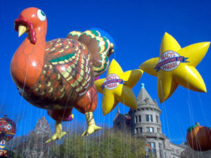turkey shape helium parade balloon and two yellow star helium parades shown in the air