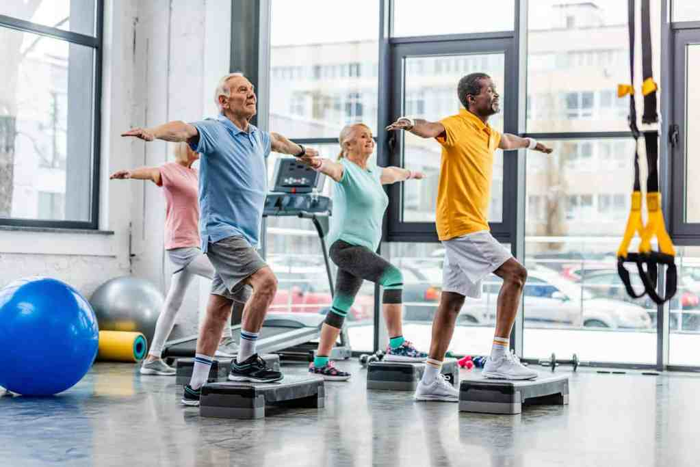 image of older adults doing step exercises in a gym