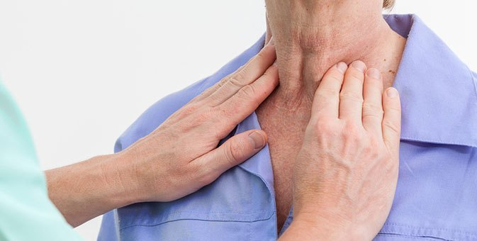 doctor feeling thyroid on patient