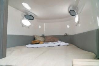 Espaçosa cabine com cama de casal e banheiro.
