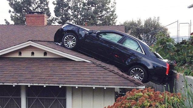 Une voiture termine sa course sur le toit d'une maison