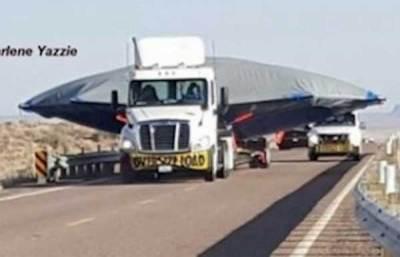 Un ovni sur une remorque suivi d'une colonne de camions noirs