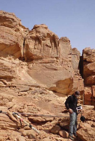 """Chercheur au pied d'un des hauts reliefs de """"Camel Site"""". © CNRS/MADAJ"""