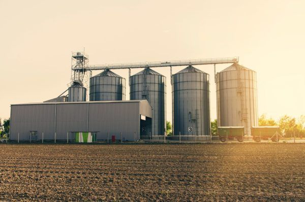 Agricultural silos on sunset and part of field and fertile soil in foreground