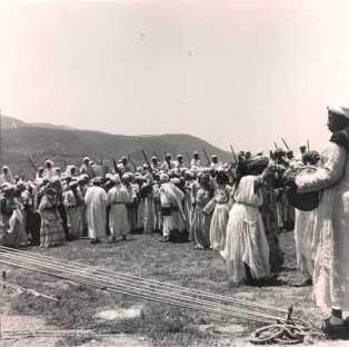 La visite du général Juin - Fête berbère (fantasia) au premier plan musiciens et danseuses au second plan, cavaliers armés tirant en l'air.
