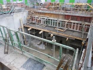 Construction de la poutre maîtresse côté Sud-Ouest montrant la préparation des planches pour le coulage de la dalle séparant le 1er niveau de parmi,g de l'espace technique