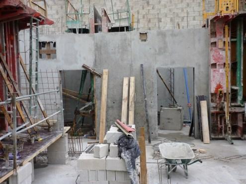 Au fond apparaissent les murs et portes d'un local technique et d'un local vélos/poussettes