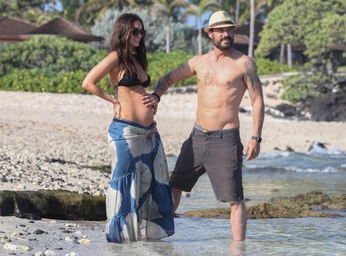 Grávida, Megan Fox passei ao lado do marido em praia no Havaí