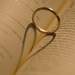 A wedding ring, pictured atop a religious text