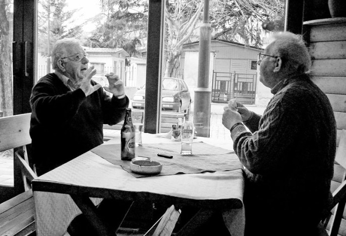 Two men are having an animated conversation whilst sitting at a table. One of the men is gesticulating with his hands to make a point.