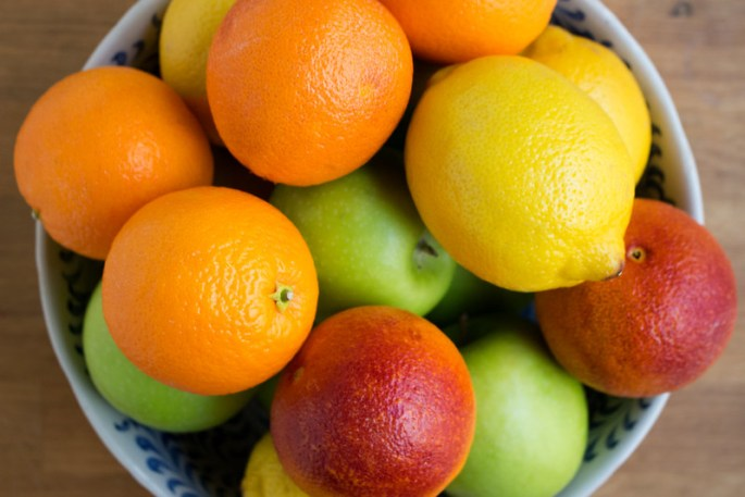 A bowl of fruit seen from above, containing a number of overlapping items including oranges, lemons and green apples.