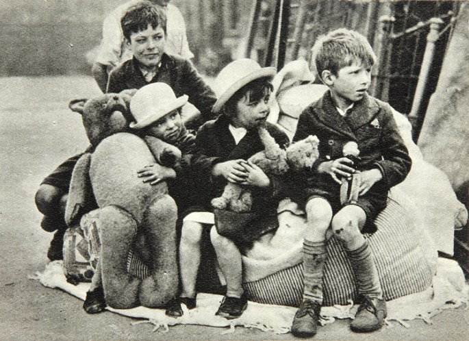 Four children, clutching various sizes of soft toy, sit in the street after a bombing.