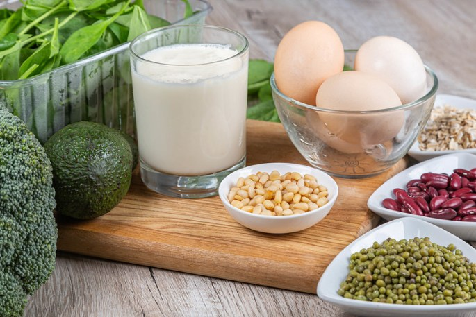 Table set with a range of foods constituting a balanced diet: pulses, eggs, milk, oats, fruit and vegetables.