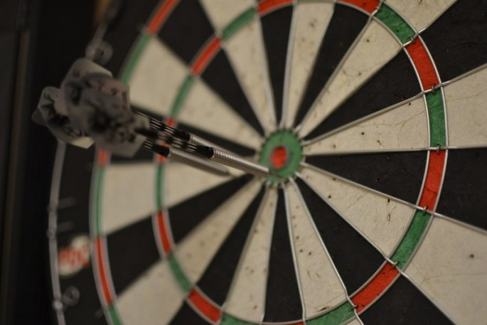 Dartboard with three darts in it, all of which have just missed the bullseye