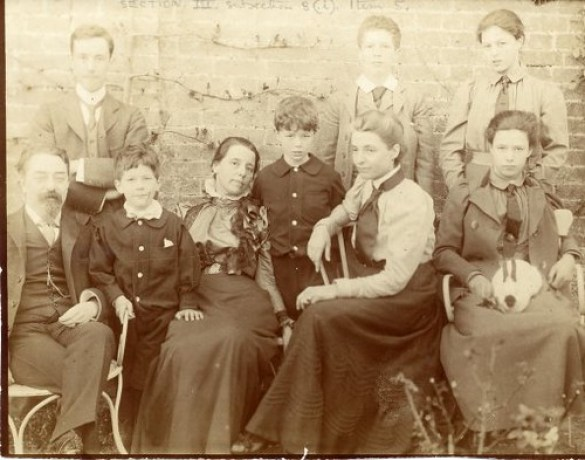 Late-Victorian sepia print of a family group, with six seated figures and three standing.