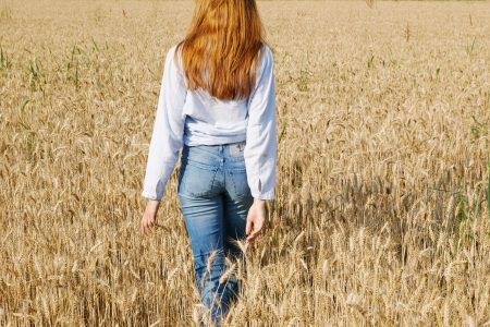 girl in a field with jeans
