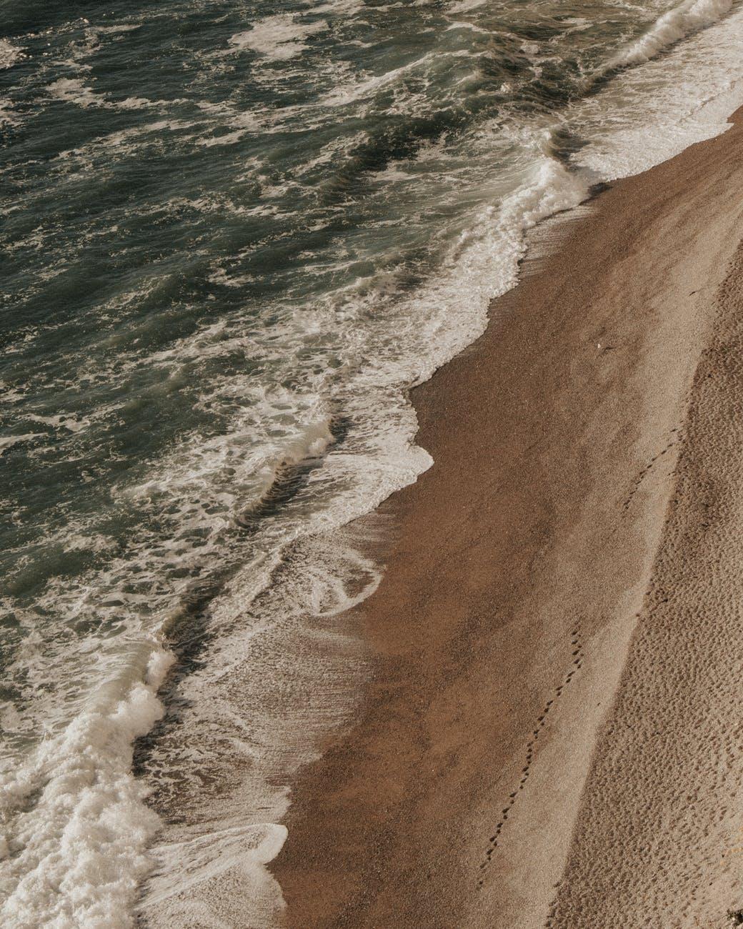 foamy sea washing sandy beach