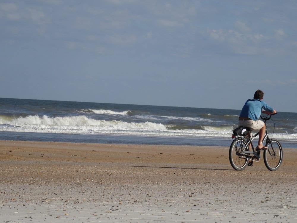 Un promeneur à vélo sur la plage