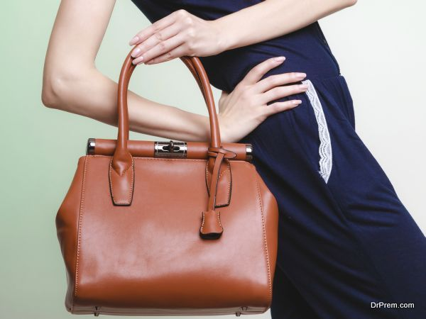 Elegant outfit. Brown leather bag in female hand