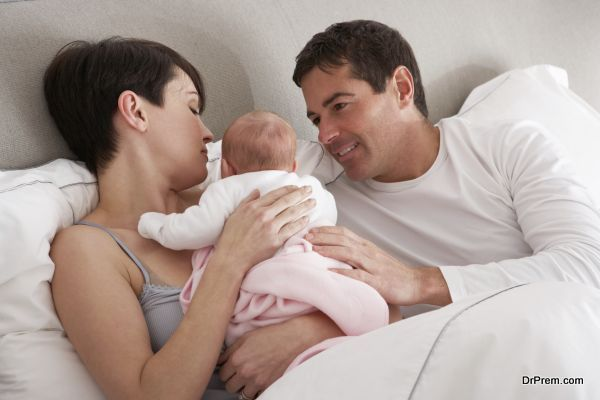 Parents Cuddling Newborn Baby In Bed At Home