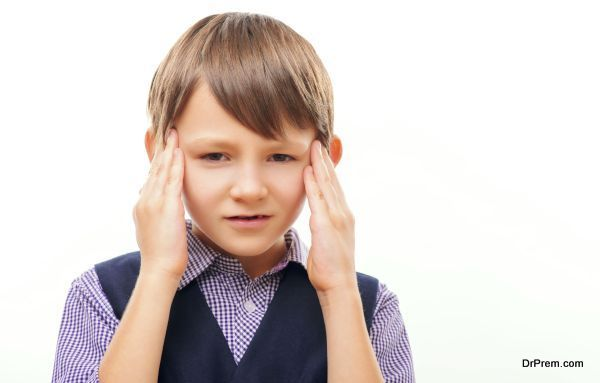 It is hard to concentrate. Closeup of stressed little boy in formal wear touching his temples with his fingers as if suffering from headache while standing isolated on white