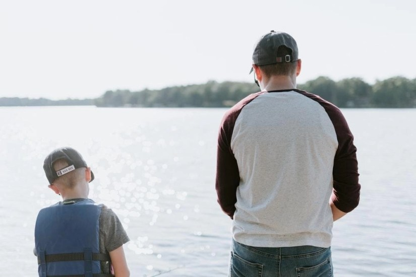 man and boy fishing on water