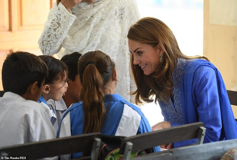 A group of girls and boys crowded around the Duchess as she sat at their classroom table for a chat this morning