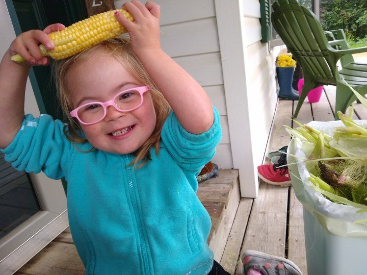 Willow holding an ear of corn on her head.