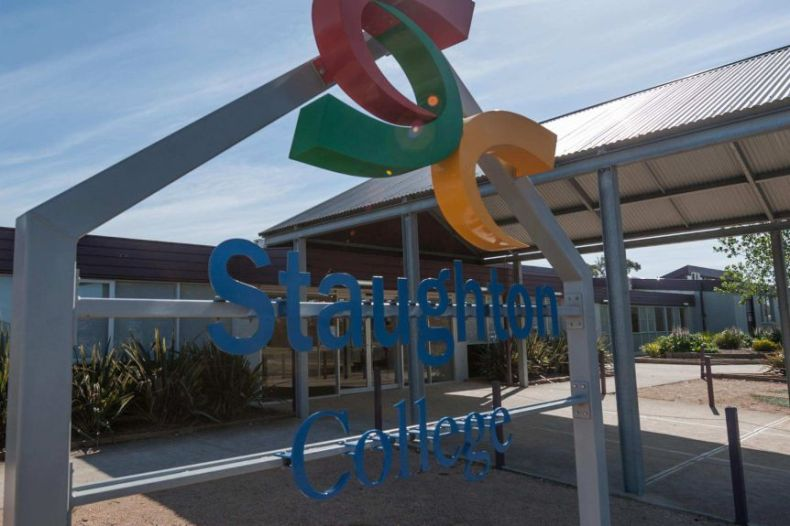 A sign outside a school says Staughton College on a sunny blue sky day.