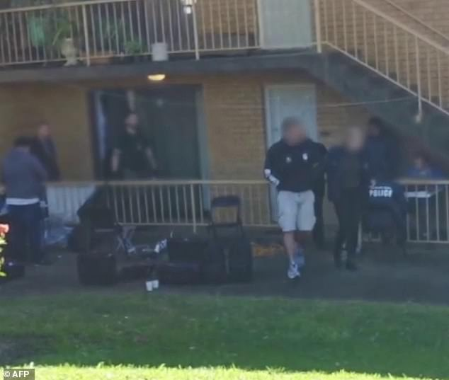 Shane William Boylan (on right, in hoodie and shorts) is walked from his home in Caringbah, in Sydney's south, to a waiting police car