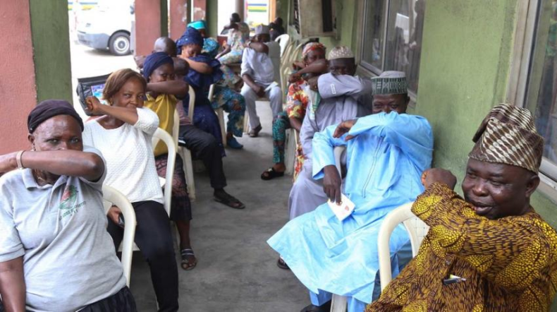 People in Nigeria's Lagos State simulate sneezing into their elbows