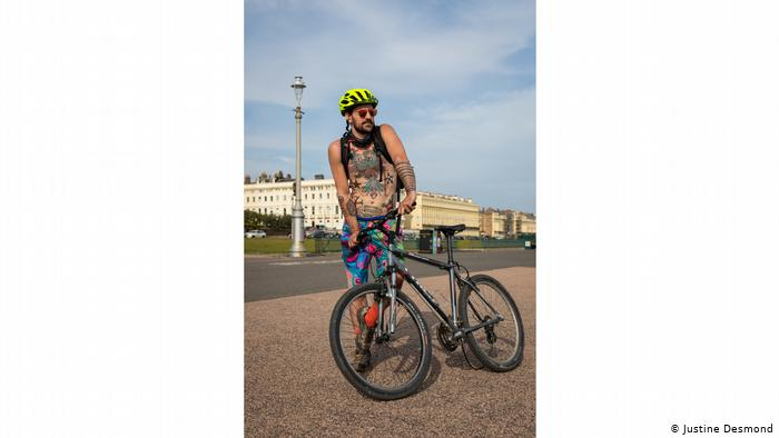 Photo from series 'People I Met on a Walk One Day During Lockdown': Heavily tatooed man with colorful shorts, a bike helmet and a bike (Justine Desmond)
