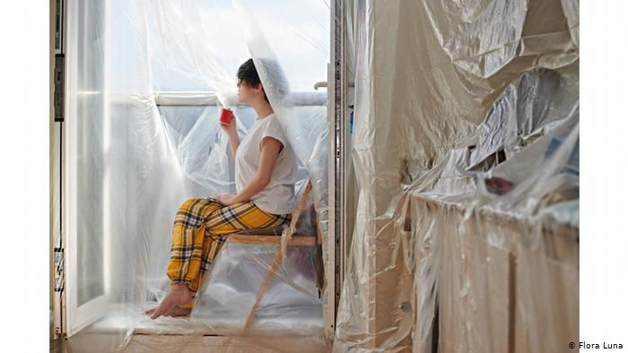 Photo from series Covered to D I S C O N N E C T: Girl sits on a wooden chair gazing through a plastic-covered window, the entire room covered in plastic as well (Flora Luna)